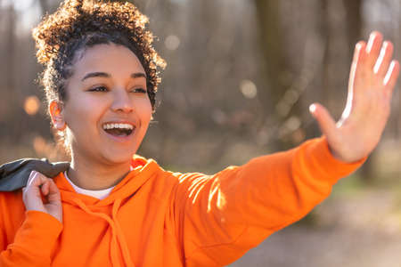 Outdoor portrait of beautiful happy mixed race biracial African American girl teenager female young woman waving and smiling with perfect teeth wearing a blue hoodie Banque d'images