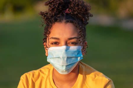 Mixed race African American teenager teen girl young woman wearing a face mask outside during the Coronavirus COVID-19 pandemic Imagens