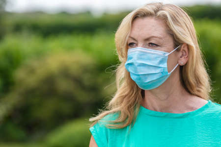 Middle aged female woman wearing face mask outside in the Coronavirus COVID-19 pandemic