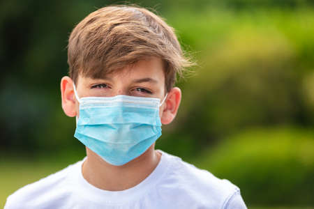 Boy teenager teen male child wearing a face mask outside during the Coronavirus COVID-19 virus  pandemic Banque d'images