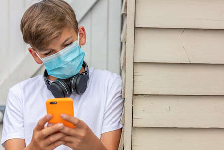 Boy teenager teen male child wearing a face mask outside during the Coronavirus COVID-19 virus pandemic while using his mobile cell phone and wireless headphones Banque d'images