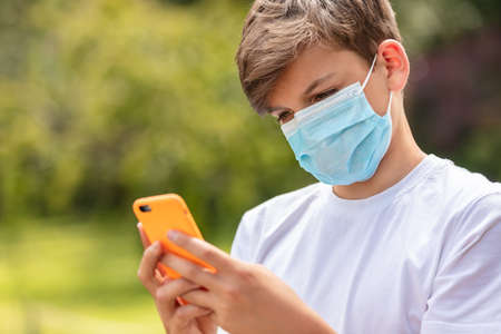 Boy teenager teen male child wearing a face mask outside during the Coronavirus COVID-19 virus pandemic while using his mobile cell phone for social media or text messaging Banque d'images