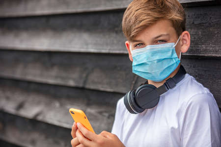 Boy teenager teen male child wearing a face mask outside during the Coronavirus COVID-19 virus pandemic while using his mobile cell phone and bluetooth wireless headphones Banque d'images