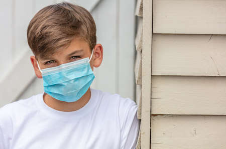 Boy teenager teen male child wearing a face mask outside leaning against the side of a house during the Coronavirus COVID-19 virus  pandemic