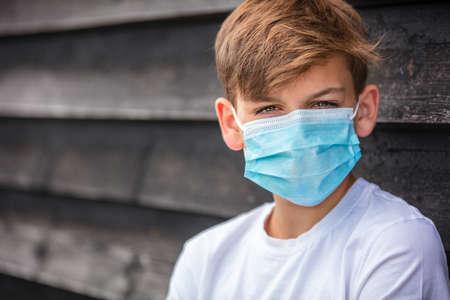 Boy teenager teen male child wearing a face mask outside during the Coronavirus COVID-19 virus  pandemic Standard-Bild