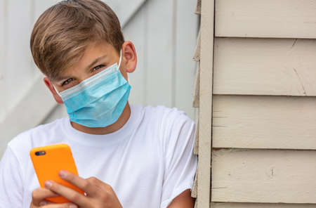 Boy teenager teen male child wearing a face mask outside during the Coronavirus COVID-19 virus pandemic while using his mobile cell phone for social media or text messaging Standard-Bild