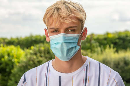 Boy teenager teen male young man wearing a face mask outside during the Coronavirus COVID-19 virus pandemic