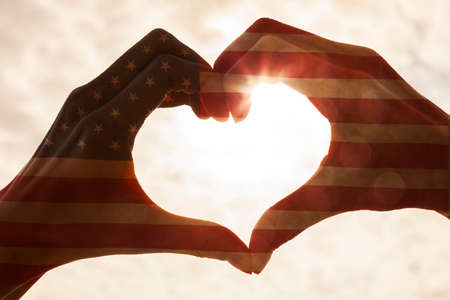 American USA flag hand heart shape silhouette made against the sun and sky of a sunrise or sunset