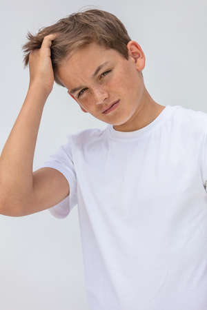 White background studio portrait of a boy teenager teen male child wearing a white t-shirt brushing his hair with his hand