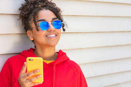 Girl teenager teen female young African American mixed race biracial woman outside smiling with perfect teeth wearing blue sunglasses and using a mobile cell phone