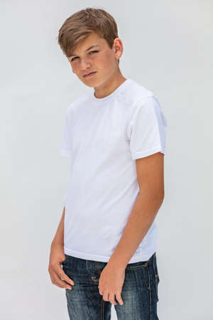 White background studio portrait of a boy teenager teen male child wearing a white t-shirt and blue jeans
