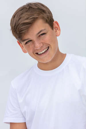 White background studio portrait of a smiling happy boy teenager teen male child with perfect teeth wearing a white t-shirt Standard-Bild