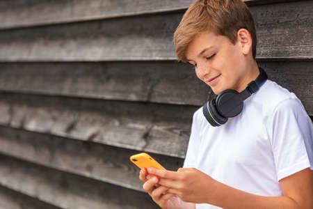 Boy teenager teen male child outside using his mobile cell phone and wireless headphones for social media