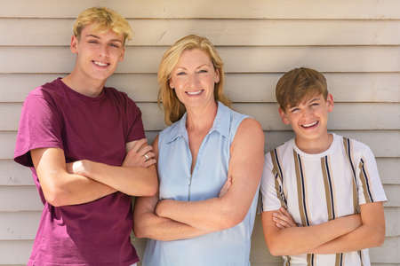 Happy mother and two teenage boys family outside arms folded smiling in summer sunshine Standard-Bild