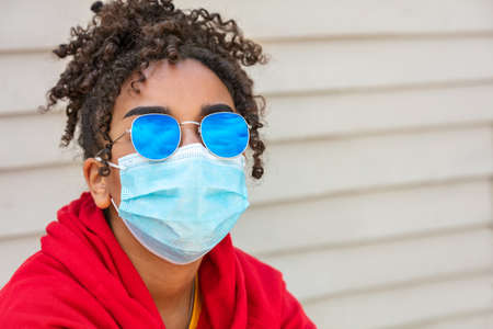 Girl teenager teen mixed race biracial African American female young woman wearing blue sunglasses and face mask in Coronavirus COVID-19 pandemic