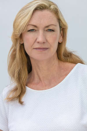 Studio portrait of an attractive middle aged blonde woman smiling on a white background