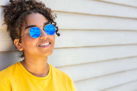 Girl teenager teen mixed race biracial African American female young woman wearing blue sunglasses smiling with perfect teeth on vacation in summer sunshine