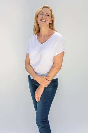 Studio portrait of an attractive middle aged blonde woman smiling on a white background wearing a white t-shirt and blue jeans