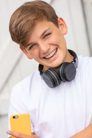 Boy teenager teen male child outside using his mobile cell phone and wireless headphones for music or social media Standard-Bild