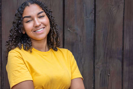 Happy portrait of a black mixed race biracial African American female young woman girl teenager teen outside smiling with perfect teeth Standard-Bild