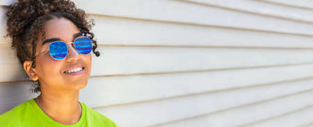 Girl teenager teen mixed race biracial African American female young woman wearing green t-shirt and blue sunglasses reflecting USA flag panoramic web banner