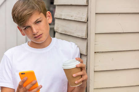 Boy teenager teen male child outside using his mobile cell phone and drinking takeout tea or coffee