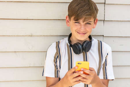 Boy teenager teen male child outside using his mobile cell phone and bluetooth wireless headphones for social media