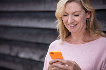 Outdoor portrait of an attractive middle aged blonde woman smiling using mobile cell phone for text messaging or social media