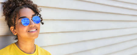 Panorama girl teenager teen mixed race biracial African American female young woman wearing yellow t-shirt and sunglasses reflecting blue sky panoramic web banner