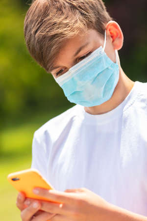 Boy teenager teen male child wearing a face mask outside during the Coronavirus COVID-19 virus pandemic while using his mobile cell phone for social media