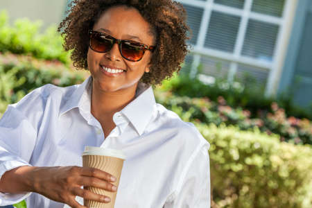 Beautiful young mixed race black African American woman smiling wearing sunglasses and drinking a takeaway cup of coffee outside