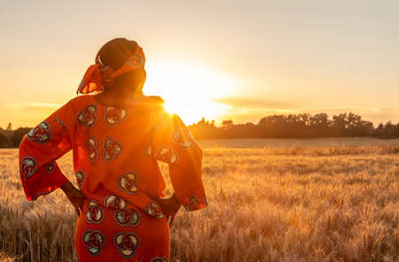African woman in traditional clothes standing with her hands on her hips in field of barley or wheat crops at sunset or sunrise
