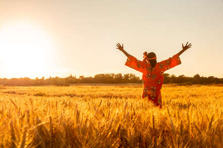 African woman in traditional clothes standing arms raised in field of barley or wheat crops at sunset or sunrise Standard-Bild