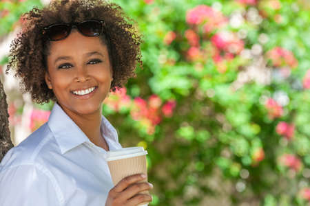 Beautiful young mixed race black African American woman smiling and drinking a takeaway cup of coffee outside
