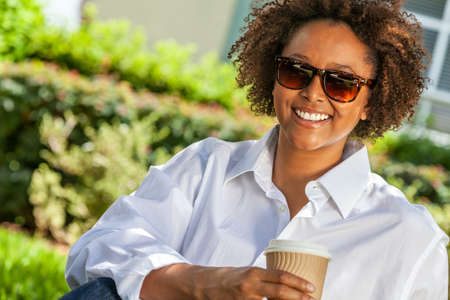Beautiful young mixed race black African American woman wearing sunglasses, smiling and drinking a takeaway cup of coffee outside Standard-Bild