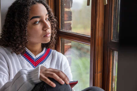 Beautiful mixed race African American girl teenager female young woman sad depressed or thoughtful looking out of a window using mobile cell phone