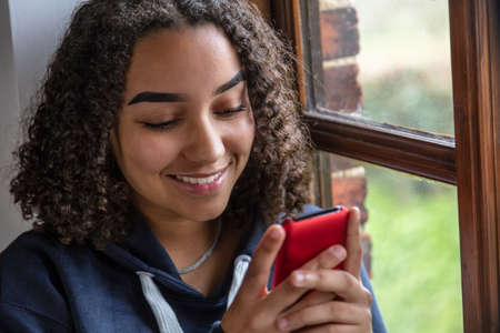 Beautiful mixed race African American girl teenager female young woman happy smiling sitting by a window using mobile cell phone