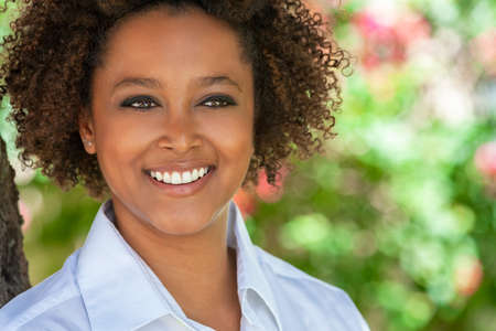 Beautiful young mixed race black African American woman with perfect teeth smiling and relaxing outside in summer sunshine