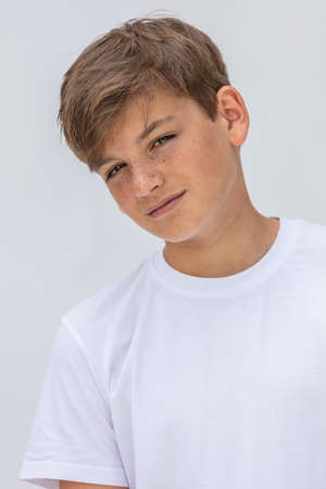 White background studio portrait of a boy teenager teen male child wearing a white t-shirt