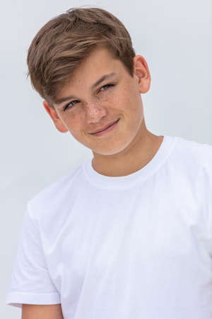 White background studio portrait of a smiling happy boy teenager teen male child wearing a white t-shirt