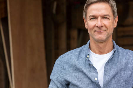 Portrait shot of an attractive, successful and happy middle aged man male wearing a blue shirt leaning on a post by a garage or barn Standard-Bild