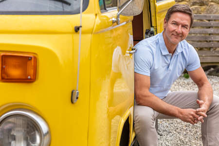 Portrait of an attractive, successful and happy smiling middle aged man male wearing a blue polo shirt, sitting in the doorway of a van or truck