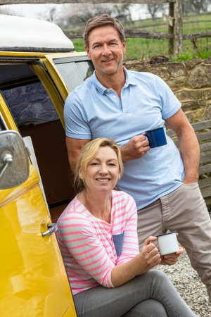 Portrait shot of an attractive, successful and happy middle aged man and woman couple together drinking tea or coffee standing by a camper van bus Standard-Bild