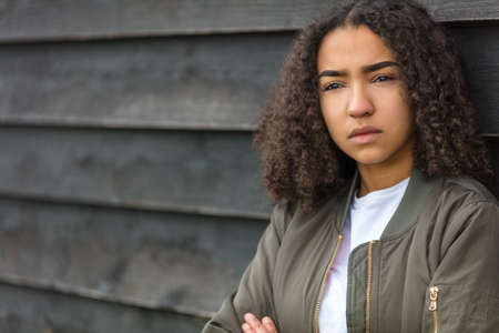 Beautiful mixed race African American girl teenager female young woman outside wearing a green bomber jacket looking sad depressed or thoughtful