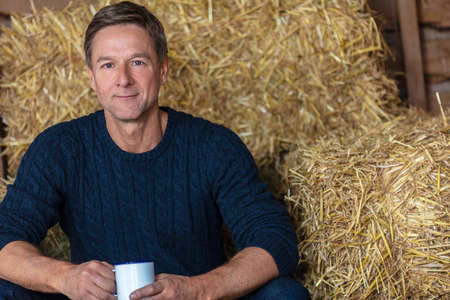 Portrait shot of an attractive, successful and happy middle aged man male wearing a blue sweater sitting on hay bales in a barn or stables drinking cup of tea or coffee 免版税图像