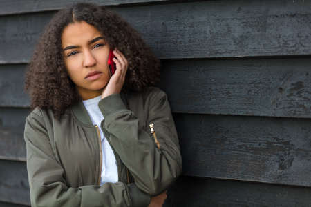 Beautiful mixed race African American girl teenager female young woman outside looking sad depressed or thoughtful talking on mobile cell phone Standard-Bild