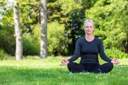 Mature middle aged fit healthy woman practicing yoga outsidein a natural tranquil green environment