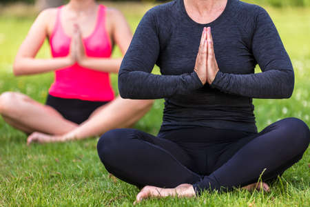 Anonymous mature fit healthy middle aged female yoga teacher yogi teaching young woman at yoga practice outside in a natural tranquil green environment Standard-Bild