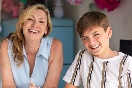 Teenage teen boy son laughing in a kitchen with his mother out of focus behind him Stock Photo