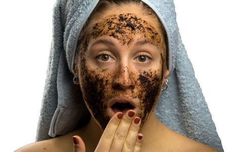 Girl after shower with a towel and different facial expressions, face with homemade coffee cream Stock Photo